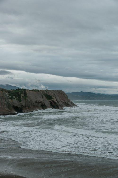 Wavy foamy sea washing rocky cliff and beach