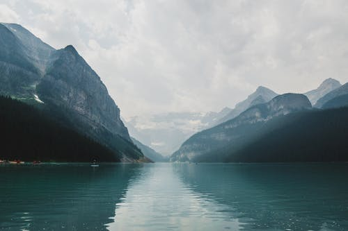 Breathtaking rocky mountains near endless rippling calm lake