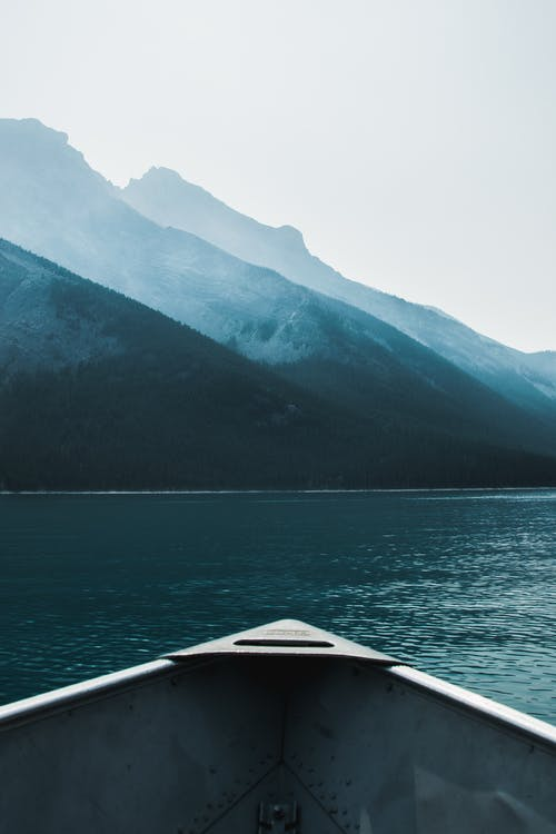 Boat tip floating on rippling lake in mountainous terrain