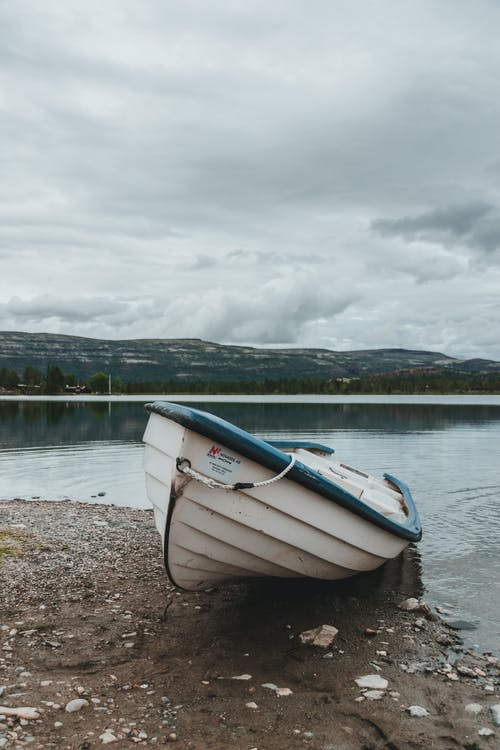Old abandoned boat on wet sandy coast near calm lake under cloudy sky