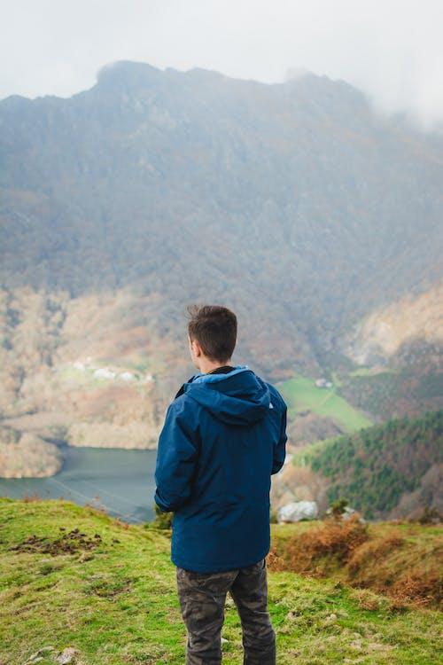 Unrecognizable man admiring view in mountainous terrain