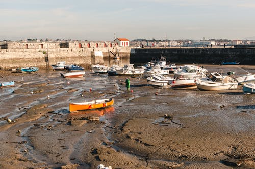 Boats on sandy surface after low tide