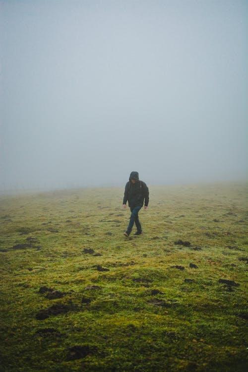 Faceless man walking on grassy hill