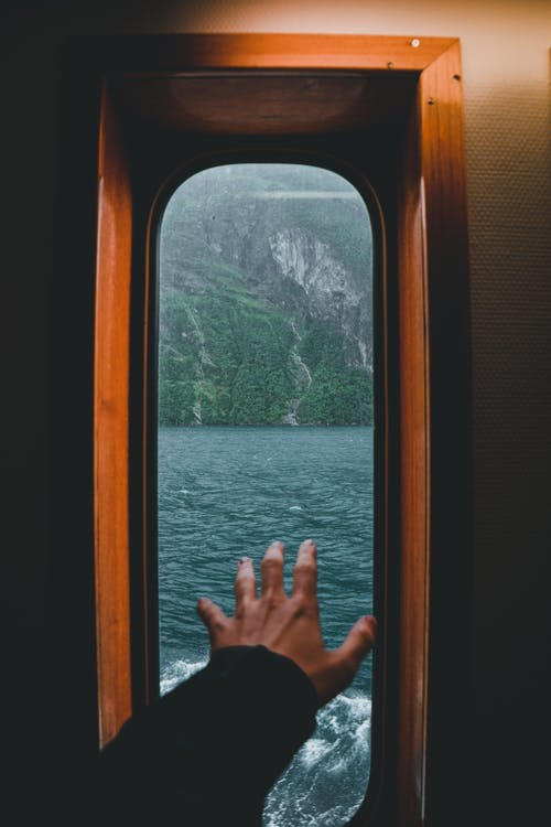 Crop unrecognizable person standing near window with hand raised inside of ship floating over water of sea near rocky formation