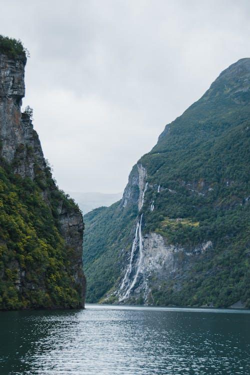 Chutes D'eau Entre La Montagne Verte Et Grise Sous Le Ciel Blanc