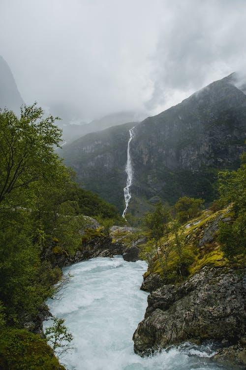 Foamy river flowing through mountainous terrain