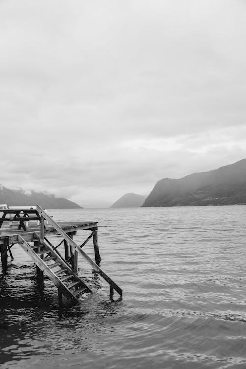 湖の木製ドックのグレースケール写真