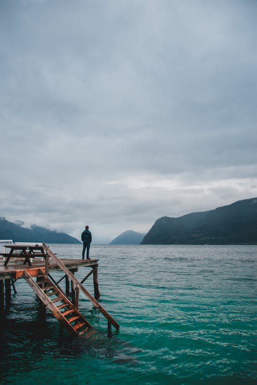 茶色の木製のドックに立っている黒いジャケットの男