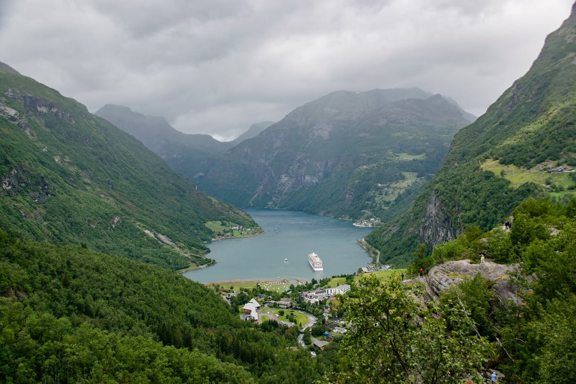 Breathtaking scenery of small village located on shore of mountainous island covered with green trees and plants under overcast sky