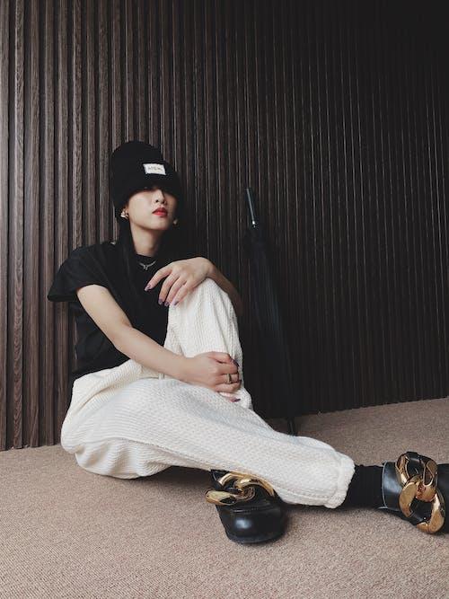 黑色頭巾和白色的裙子,坐在棕色地毯上的女人