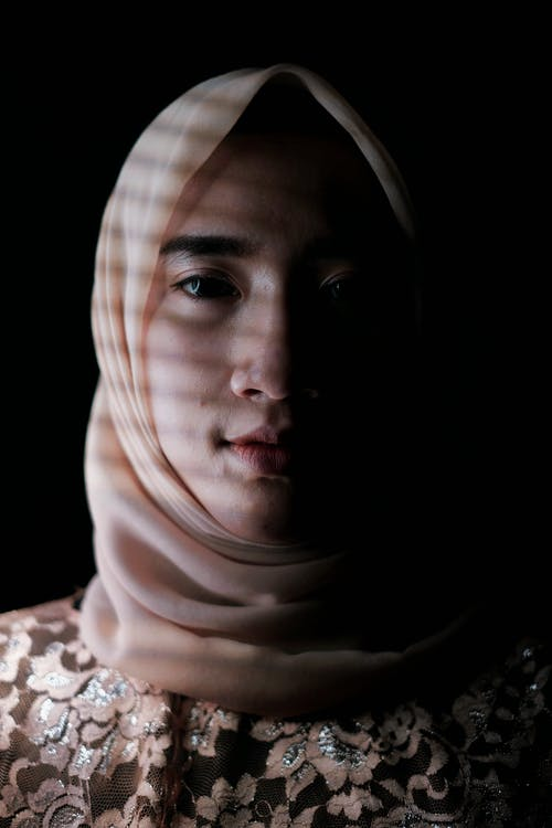 Calm young Islamic female wearing light headscarf looking at camera and standing in dark room with shadows on face