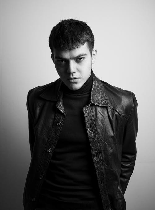Serious male in leather jacket standing in studio