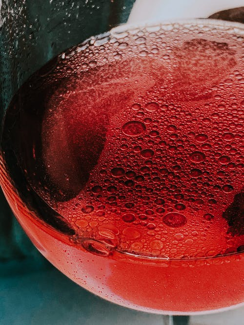 Glass of red sparkling wine served in table