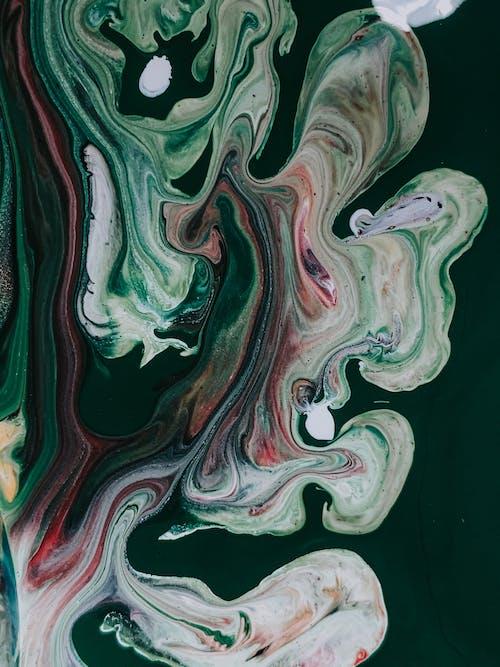 Colorful acrylic paints mixed in technique fluid art