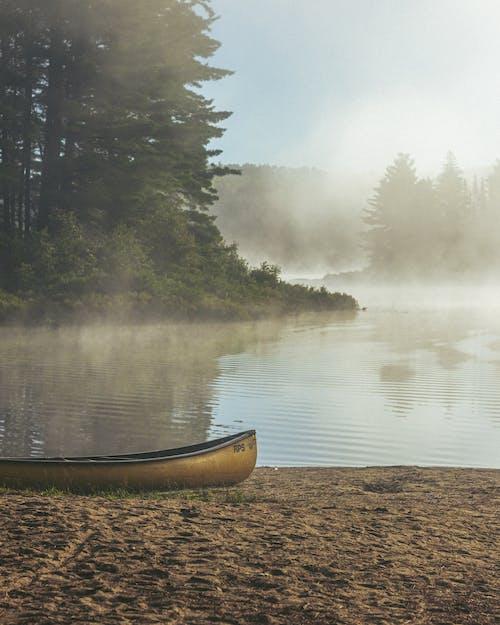 Brown Canoe on Brown Sand Near Lake