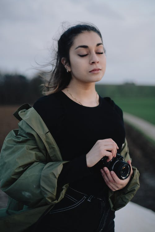 Young sensitive female photographer with modern photo camera standing with eyes closed in vast peaceful countryside at twilight