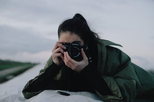 Unrecognizable woman taking photo on roof in evening countryside