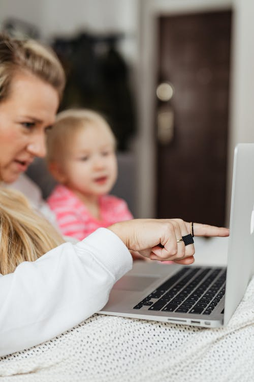 A Mom Besides Her Child Pointing to the Laptop Screen