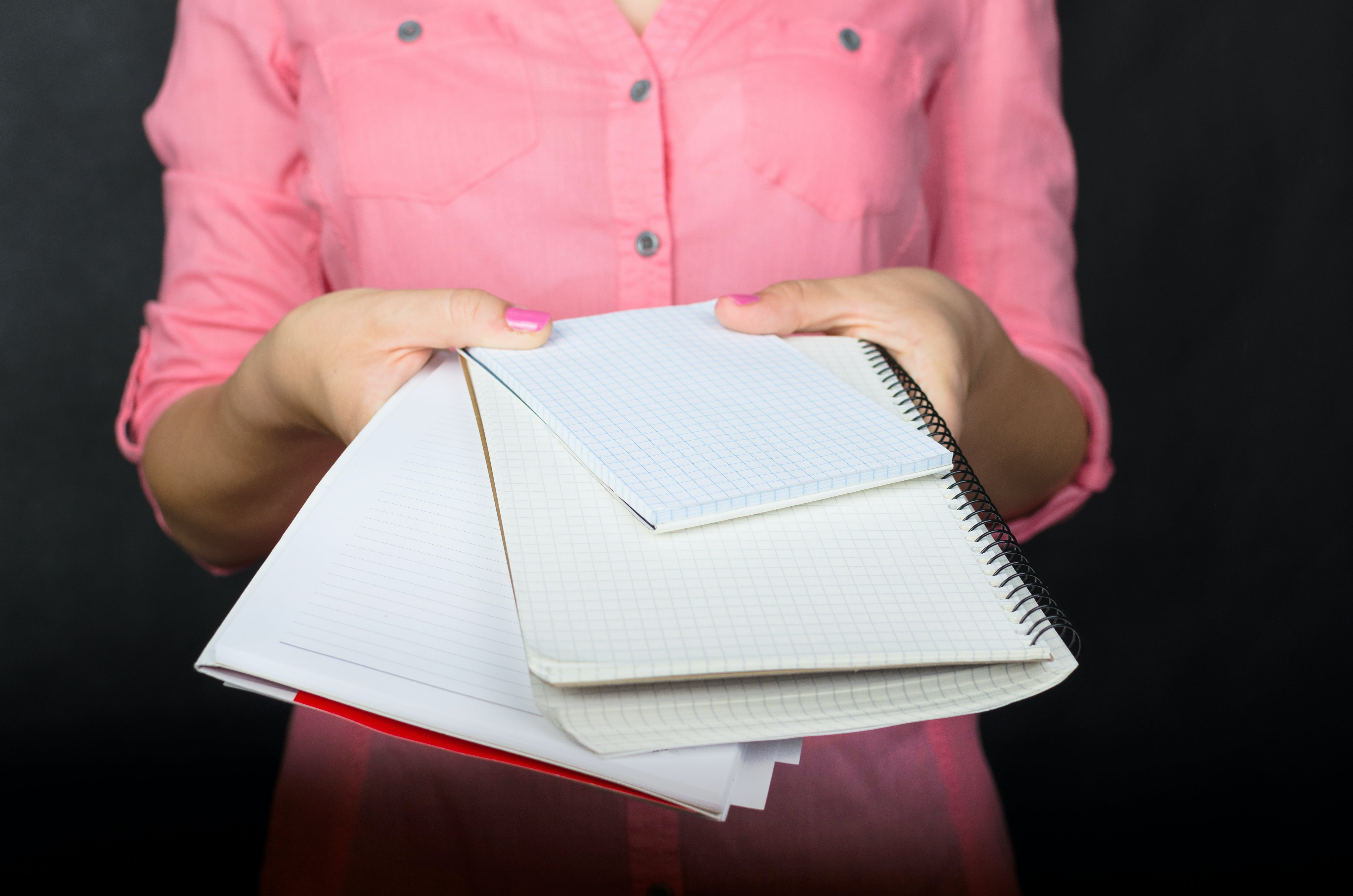 Woman Holding Three Notebooks