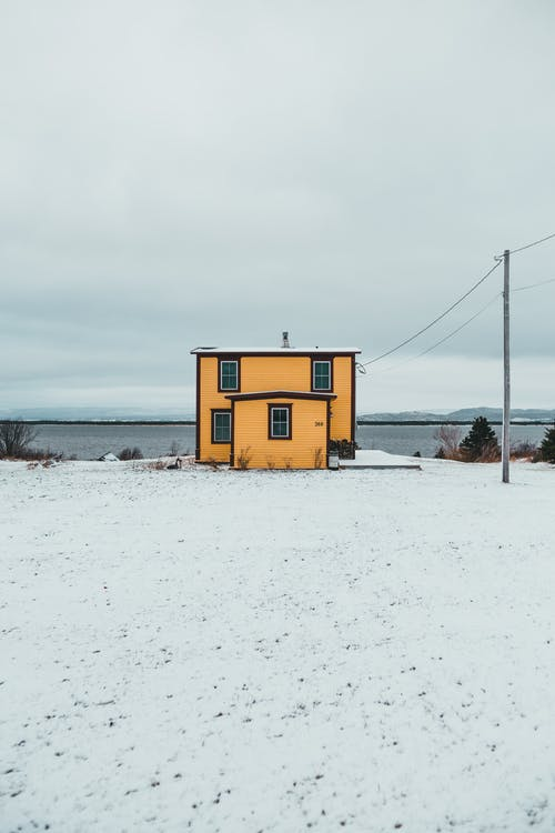Exterior of small house located on snowy waterside near trees and calm river against cloudy sky on cold winter day