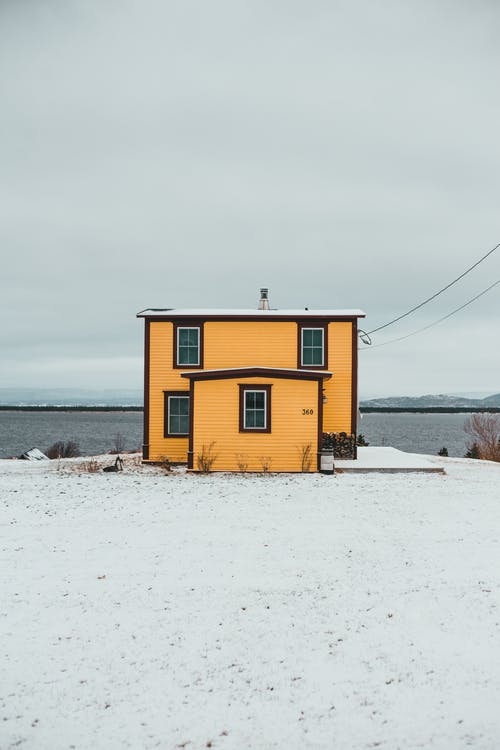 Exterior of yellow cottage located on shore covered with snow near rippling river against cloudy sky on cold winter day