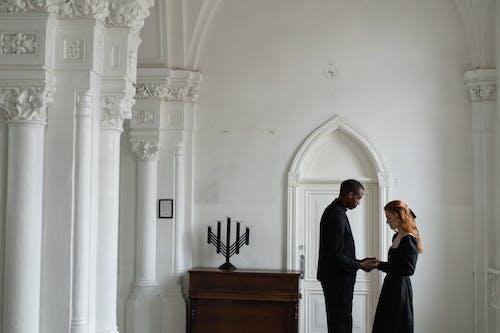 Man in Black Suit Standing Beside Woman in White Dress