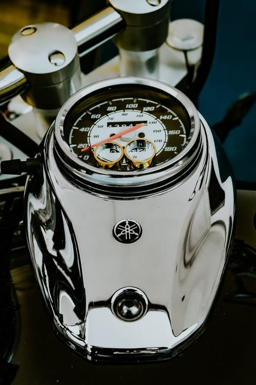 From above fancy golden wedding rings placed on contemporary powerful motorbike speedometer for proposal