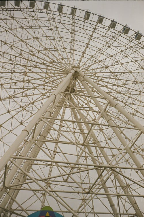 Low angle of huge Ferris wheel with cabins in amusement park against grey sky