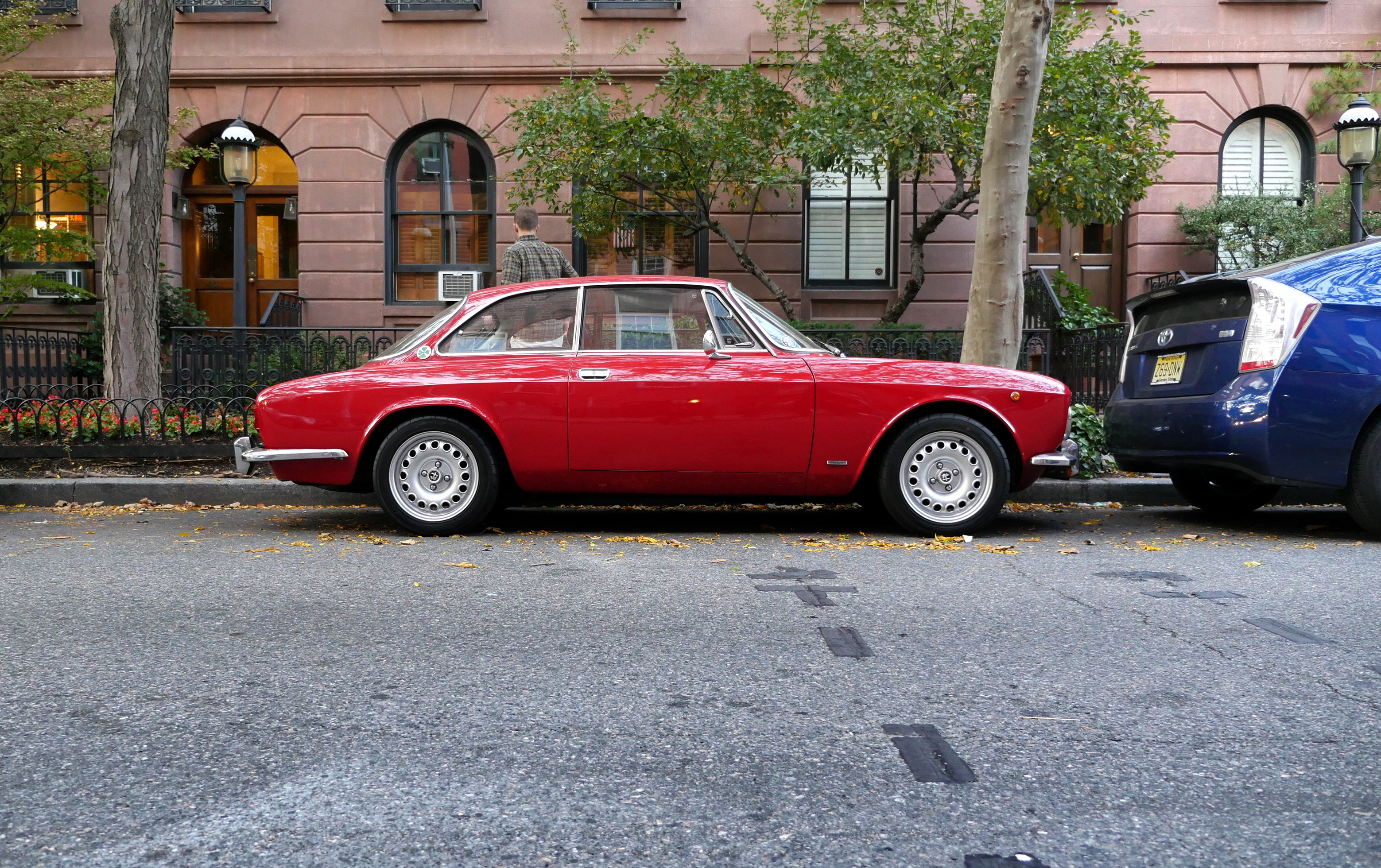 Classic Red Coupe Parked Near Blue Toyota Prius on Sidewalk