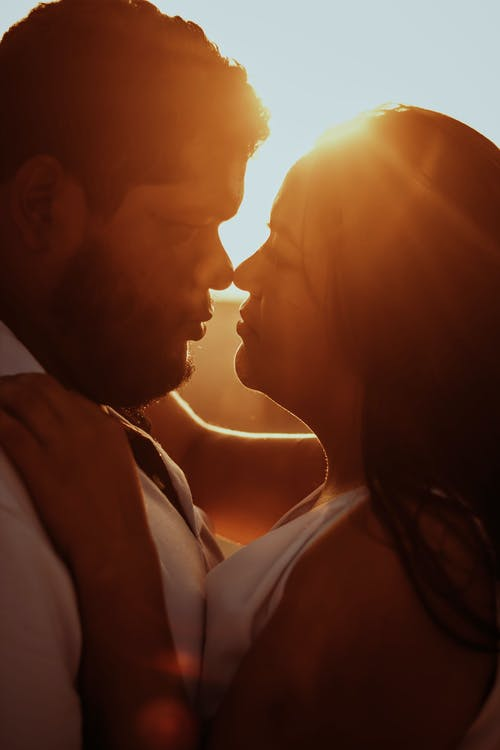 Side view crop romantic ethnic couple cuddling and looking at each other with tenderness while standing face to face in nature during bright sunset