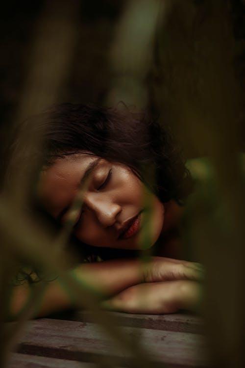 Sensitive ethnic woman lying on boardwalk in nature