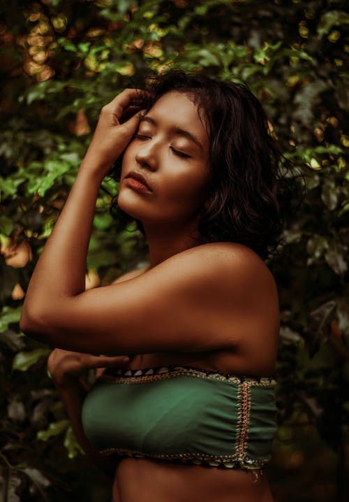 Sensual ethnic woman touching face gently in lush garden