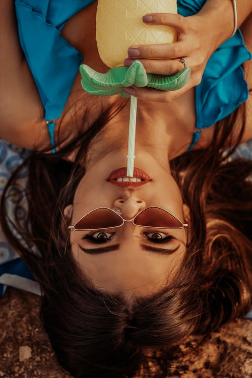 Top view beautiful young female in trendy sunglasses looking at camera and drinking refreshing beverage from creative bottle while lying on ground