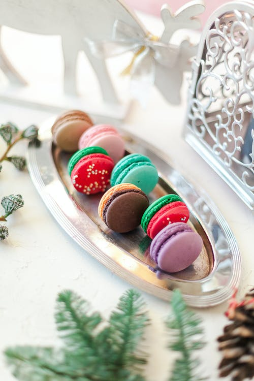 Composition of colorful palatable macaroons served on steel tray on white table in light room
