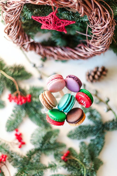 Top view composition of delicious fresh macaroons on sticks placed near Christmas decorations and fir twigs