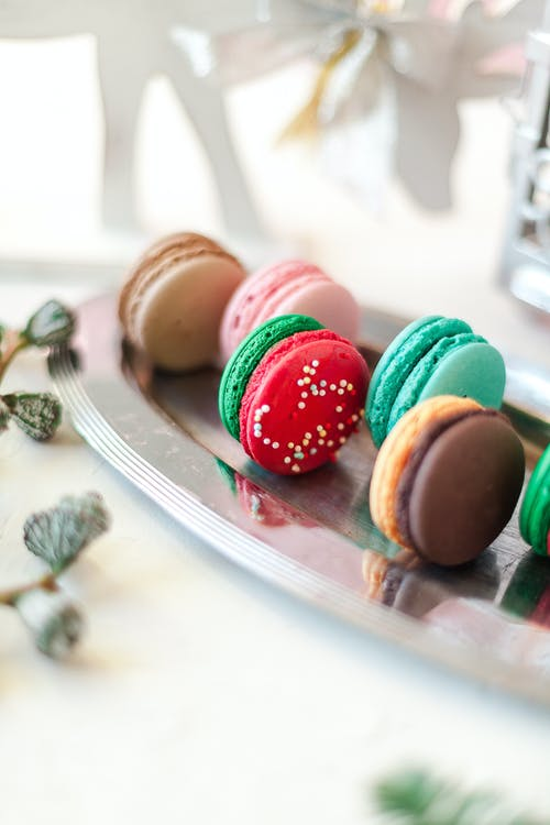 Yummy macaroons on steel tray in light room