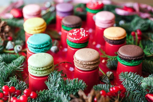 Collection of delicious yummy macaroons represented on red serving board decorated with fir branches