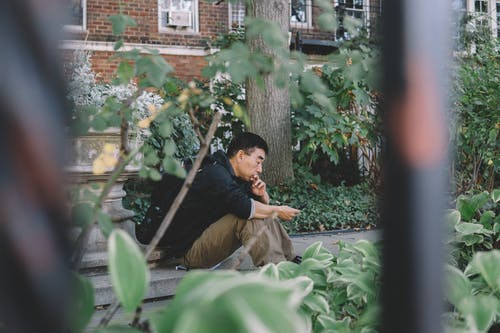 Man Seating Outdoor Beside Green Leafed Plants