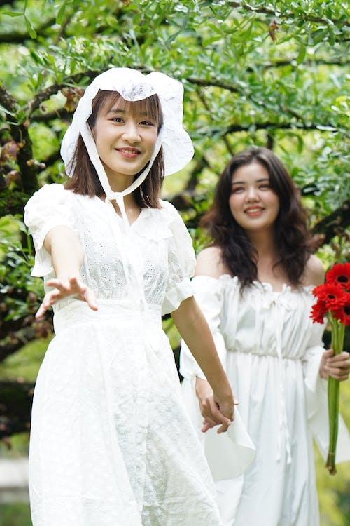 2 Women in White Dresses Posing for Photo