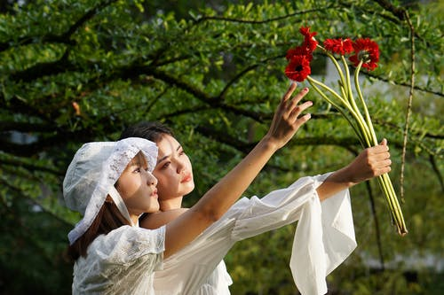 Woman in White Wedding Dress Holding Red Flower