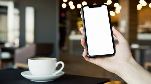 Person Holding Black Iphone with Blank Screen