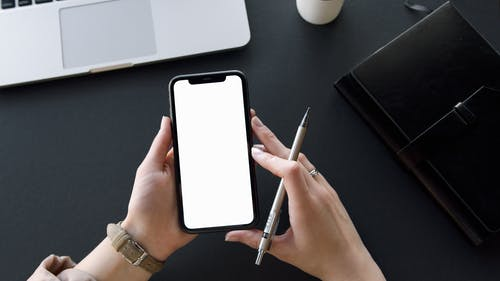 Person Holding Black Iphone and Pen
