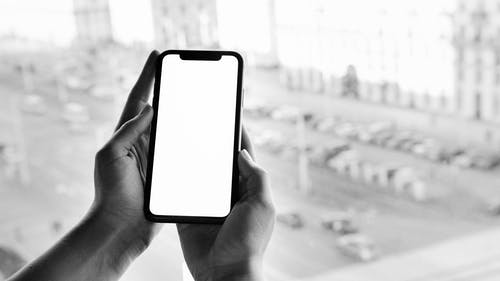 Grayscale Photo of Person Holding Smartphone
