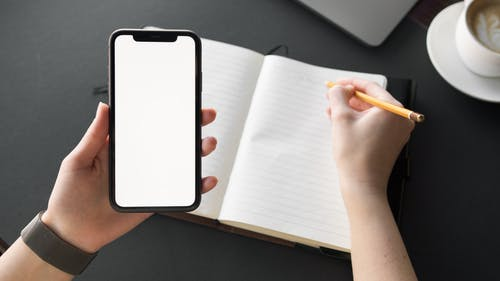 Person Holding Mobile Device while Writing on Stationery