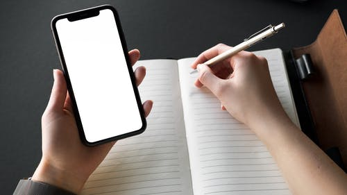 Person Holding Iphone while Writing on Journal