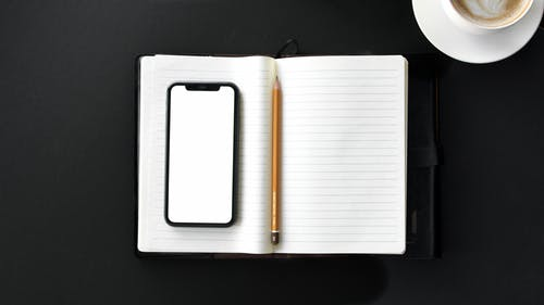 Black Iphone on Top of Stationery