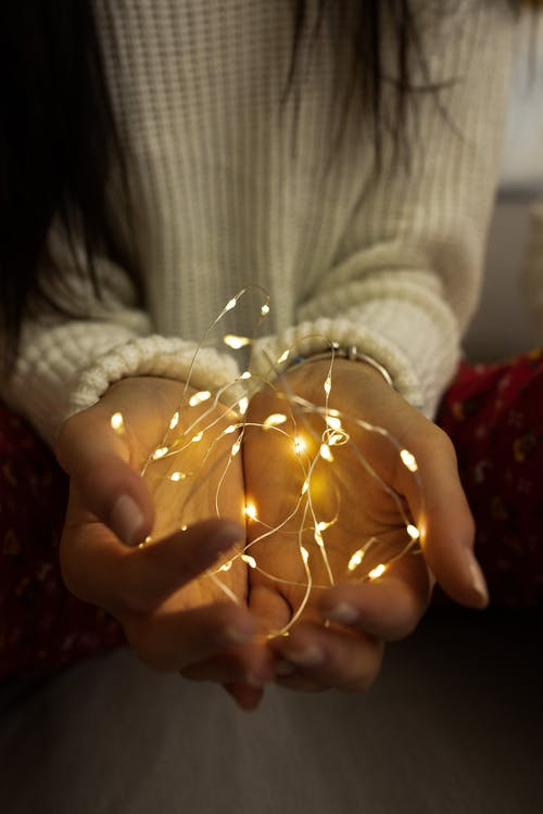 Woman in White Sweater Holding String Lights