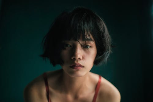 Sad young Asian female in red top looking at camera in studio with green wall
