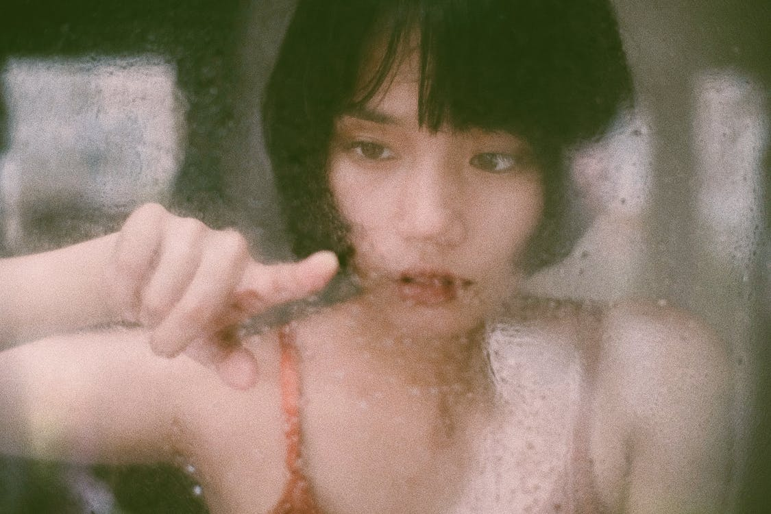 Through window of young Asian woman drawing on  wet glass with finger in soft light