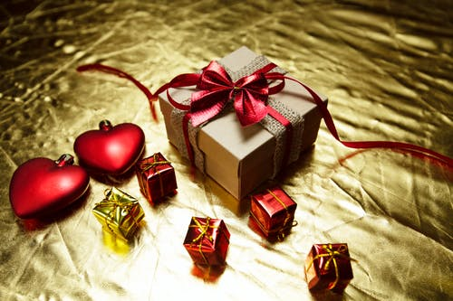 From above of various wrapped gift boxes with bows placed on shiny golden surface with red heart shaped Christmas tree baubles